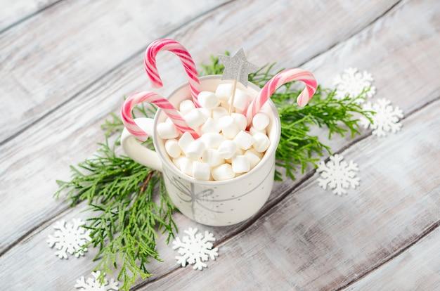 Ano novo ou natal. composição com marshmallows e bastões de doces em um fundo de madeira. Foto Premium