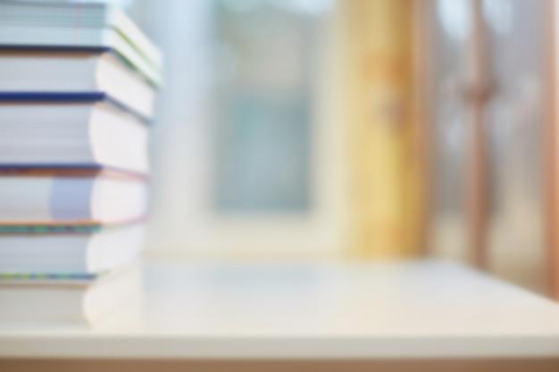Antecedentes sobre o tema da formação, educação. mesa com livros, estante e janela em desfocagem. conceito de escola ou cartão com o início da aprendizagem. Foto Premium
