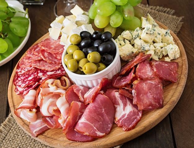 Antepasto de catering prato com bacon, carne seca, salame, queijo e uvas em uma mesa de madeira Foto gratuita