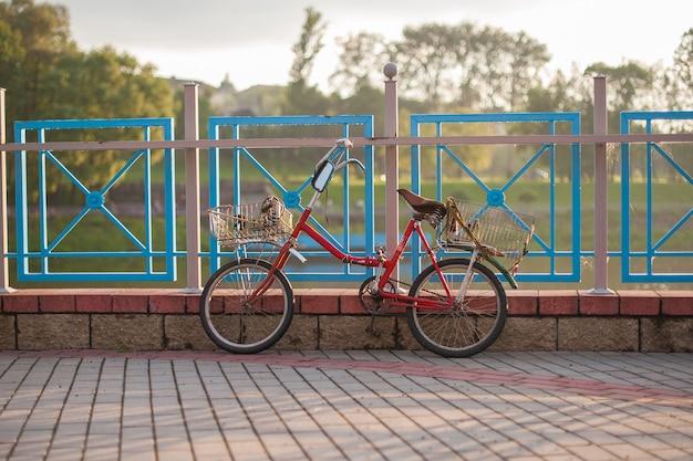 Antiga bicicleta vermelha com cestas fica em cima da muro ao pôr do sol Foto Premium