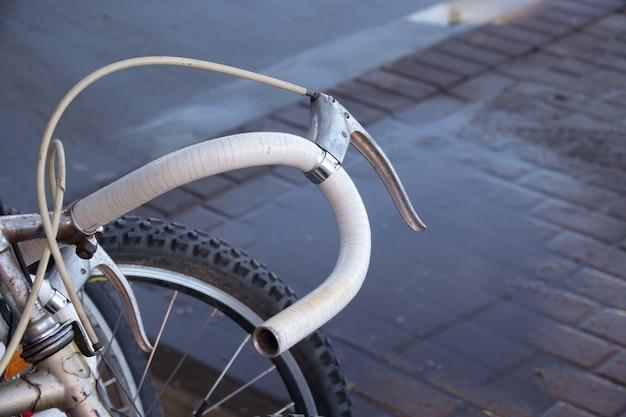 Antiga bicicleta vintage enferrujada perto do muro de concreto Foto Premium