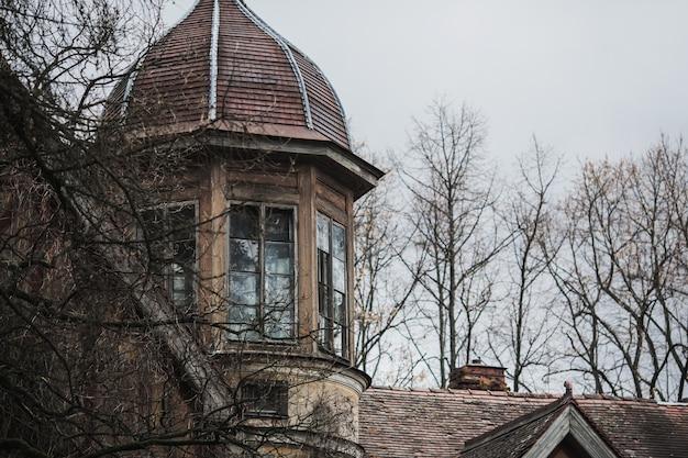 Antiga casa gótica abandonada. a mansão em ruínas fica no parque. janela misteriosa. fundo gótico. lugar de festa de halloween. casa assustadora. janela e telhado do palácio velho. edifício medieval assustador Foto Premium
