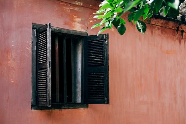 Antiga janela e parede rosa em hoi an, vietnã Foto gratuita