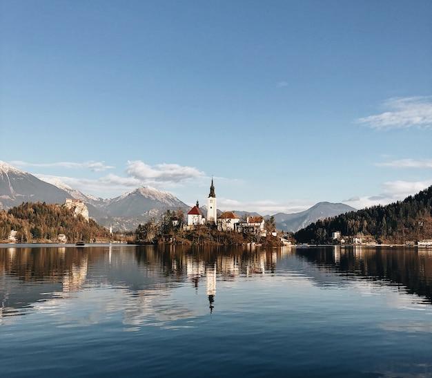 Antigo castelo cercado por um cenário montanhoso, refletindo no lago Foto gratuita