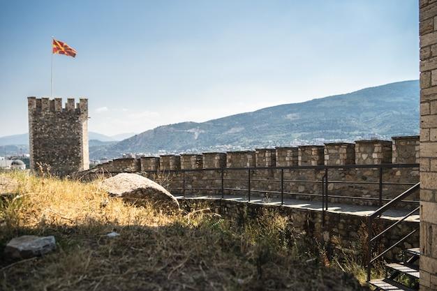 Antigo castelo com a bandeira da macedônia cercado por colinas cobertas de vegetação Foto gratuita