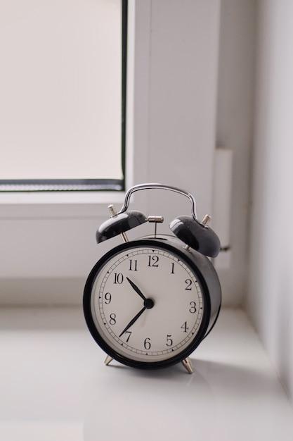 Antigo despertador mecânico preto e branco relógio está no peitoril da janela Foto Premium