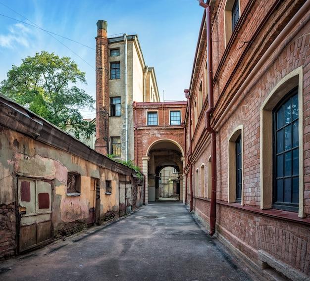 Antigo pátio de tijolos de um edifício residencial às margens do rio moika em são petersburgo Foto Premium