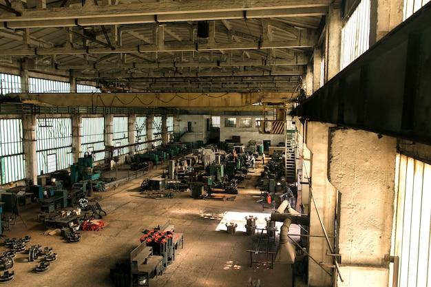 Antigo salão da fábrica com equipamentos e máquinas e trabalhadores Foto gratuita