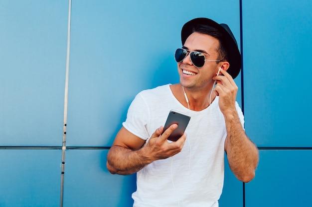 Ao ar livre foto de cara atraente em óculos de sol, ouvindo música em fones de ouvido Foto gratuita