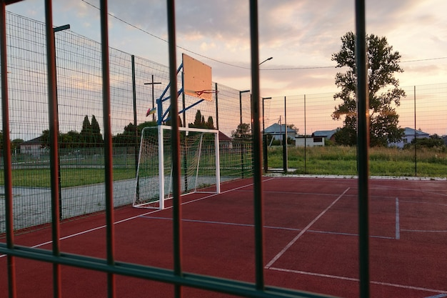 Ao ar livre mini quadra de futebol e basquete com portão bola e cesta cercada com alta cerca de proteção. Foto Premium