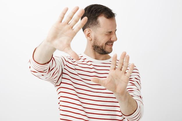 Apague a luz. retrato de um modelo masculino desconfortável e descontente em traje casual, puxando as palmas das mãos e virando o rosto para se esconder da luz brilhante ou soco Foto gratuita