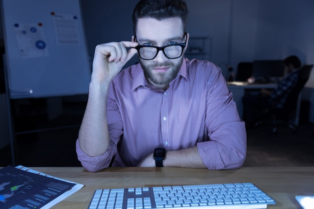 Aparência inteligente. homem bonito e inteligente sentado em frente ao computador e consertando os óculos enquanto olha para você Foto Premium