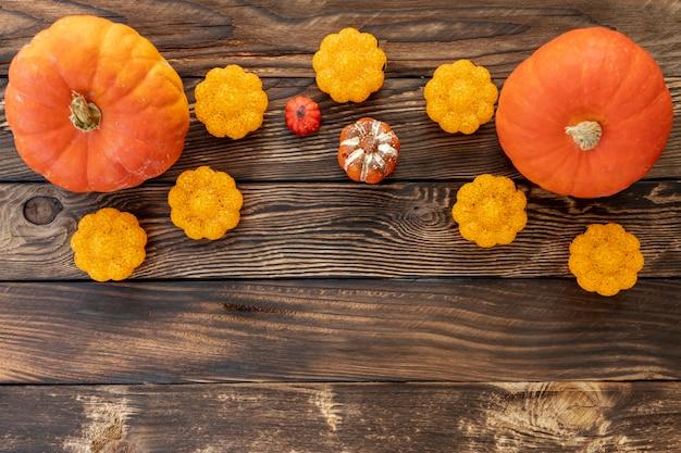 Apartamento colocar abóboras coloridas sobre fundo de madeira Foto gratuita