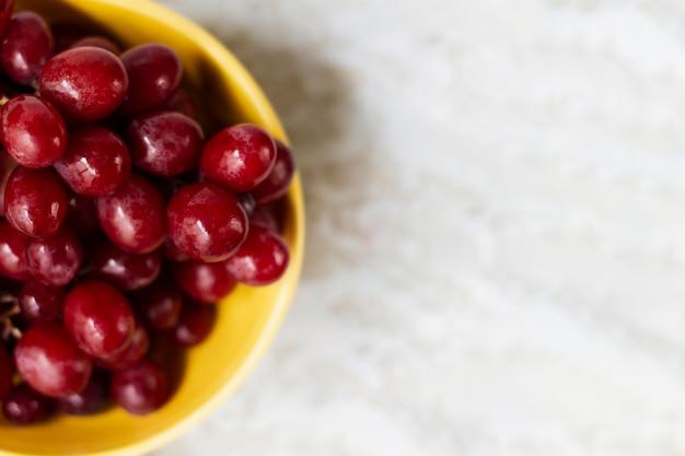 Apartamento colocar uvas vermelhas em tigela Foto gratuita