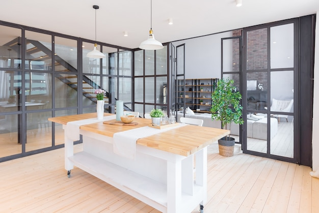 Apartamento de dois andares com design moderno e moderno, com grandes janelas altas. a elegante sala de estar e cozinha em cores vivas são despojadas por uma divisória de vidro. quarto no segundo andar. Foto Premium