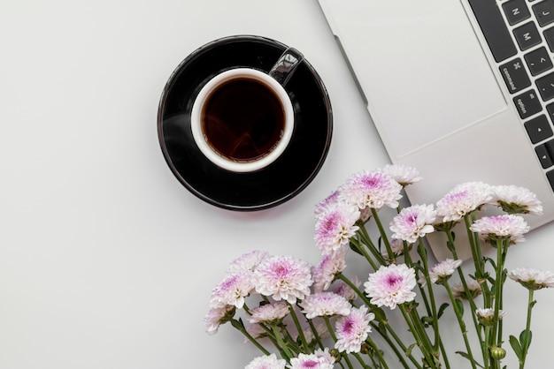 Apartamento leigos com flores e laptop com café Foto gratuita