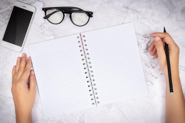 Apartamento leigos da mão de uma mulher escrevendo em um caderno de página em branco em branco na mesa de mármore branco Foto Premium