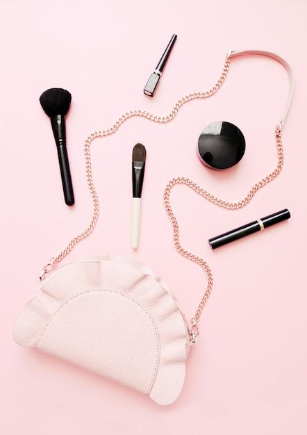 Apartamento leigos de acessórios de moda feminina, produtos de maquiagem e bolsa em fundo de cor pastel Foto Premium