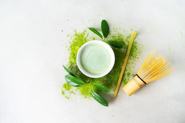 Apartamento leigos de chá verde orgânico matcha em pó com ferramentas japonesas chasen whisk de bambu Foto Premium