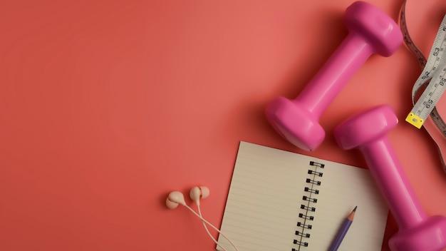 Apartamento leigos de equipamentos de fitness halteres notepad lápis e fone de ouvido no fundo rosa Foto Premium