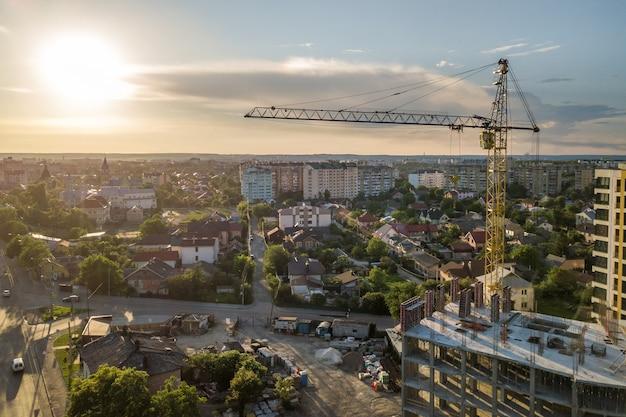 Apartamento ou prédio alto em construção. paredes de tijolo, janelas de vidro, andaimes e pilares de suporte de concreto. guindaste de torre no espaço da cópia do céu azul brilhante Foto Premium
