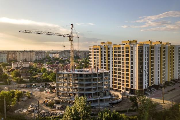 Apartamento ou prédio alto em construção. paredes de tijolo, janelas de vidro, andaimes e pilares de suporte de concreto. guindaste de torre no fundo brilhante do espaço da cópia do céu azul. Foto Premium