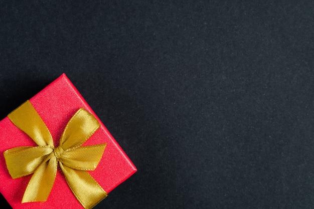 Apenas um presente em um fundo preto com espaço para o texto à direita. Foto Premium