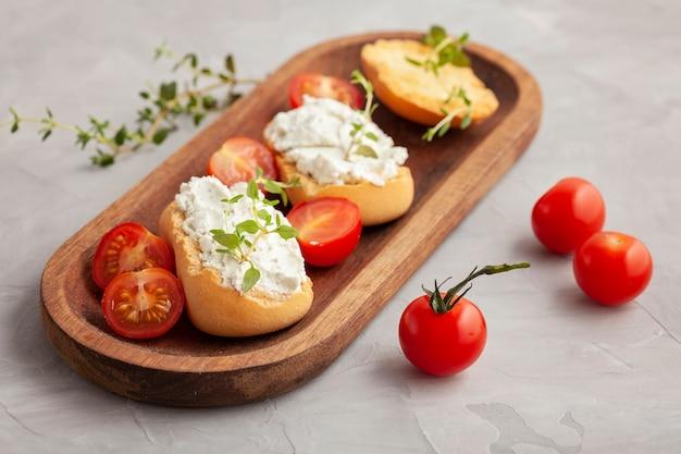 Aperitivo italiano bruschetta de pão torrado com creme chease e tomate. refeição deliciosa e saudável, copie o espaço Foto Premium