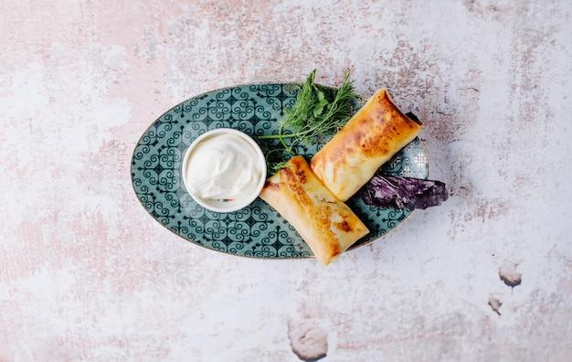 Aperitivo russo blinchik em crepes com ervas e iogurte. Foto gratuita