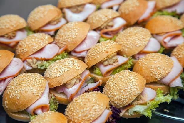 Aperitivos frios em uma bandeja. hambúrguer com bacon e ervas em várias linhas Foto Premium