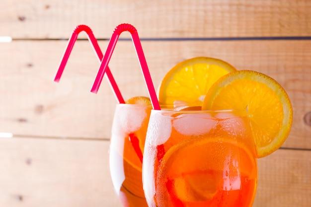 Aperol spritz cocktail em placas de madeira. dois copos com cocktail alcoólico de verão com fatias de laranja. coquetel italiano Foto Premium