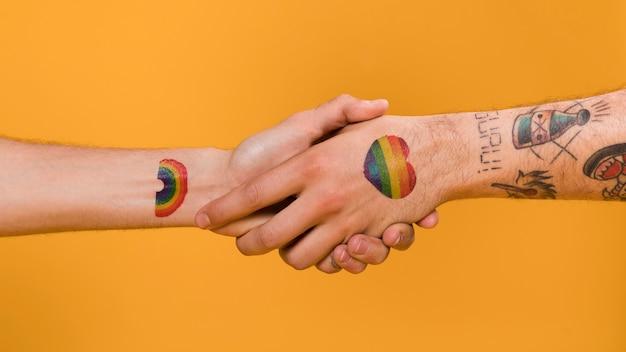 Aperto de mão de duas mãos de homem com orgulho gay padrão multicolorido Foto gratuita