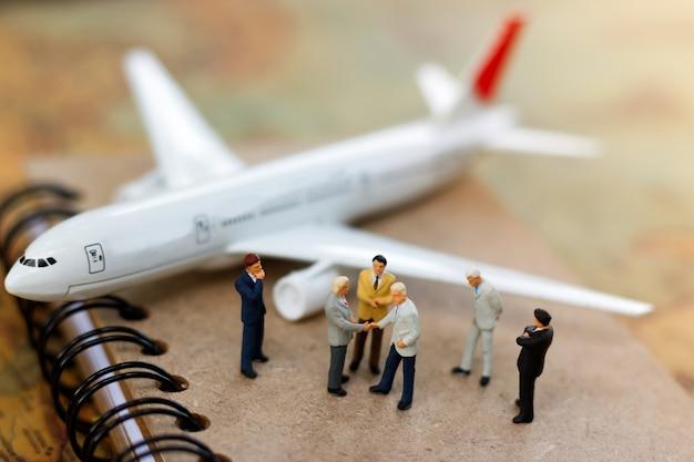 Aperto de mão diminuto do homem de negócios no livro com avião. Foto Premium