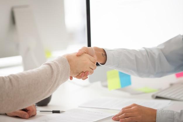 Aperto de mão do homem de negócios e da mulher de negócios após ter assinado o contrato ou a negociação bem sucedida Foto gratuita