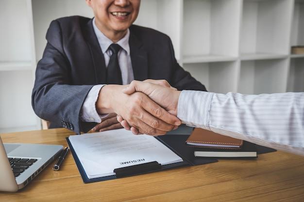 Aperto de mão durante a entrevista de emprego, candidato apertando as mãos com o entrevistador ou empregador Foto Premium