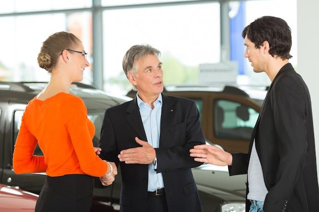 Aperto de mão homem maduro com jovem casal e auto na concessionária Foto Premium