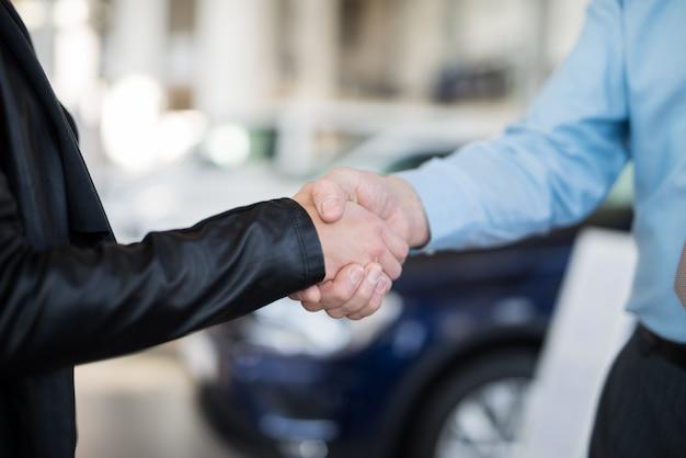 Aperto de mão para selar o acordo para um carro novo Foto Premium