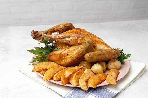 Apetitoso frango assado com alho batatas e cebolas Foto Premium