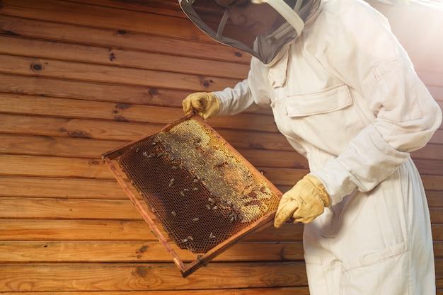 Apicultor feminino jovem segurar a moldura de madeira com favo de mel, coletar mel, conceito de apicultura Foto Premium