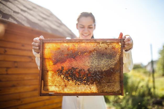 Apicultor feminino jovem segurar a moldura de madeira com favo de mel. colete mel. apicultura. Foto Premium