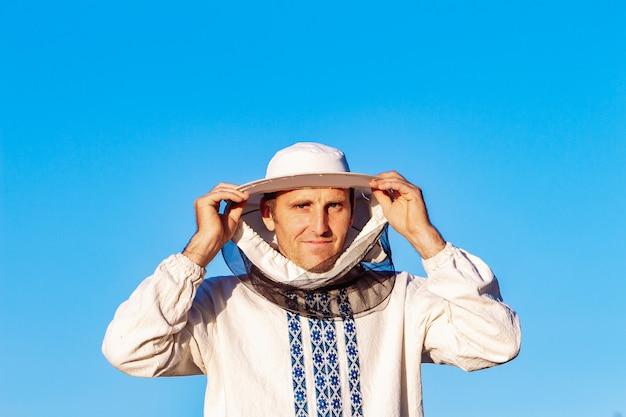 Apicultor jovem trabalhando no apiário Foto Premium