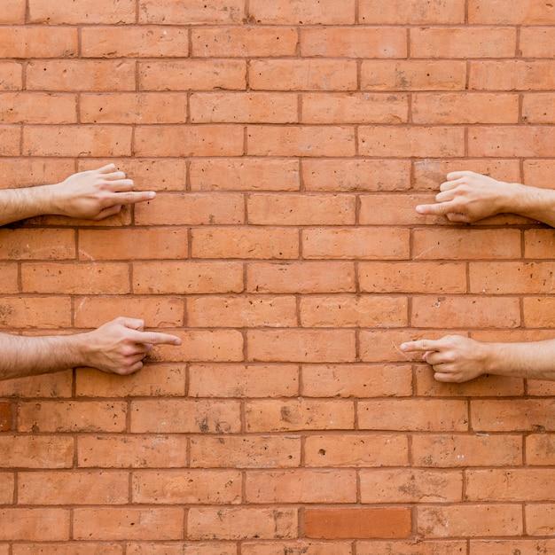 Apontando os dedos um para o outro na parede de tijolo Foto gratuita