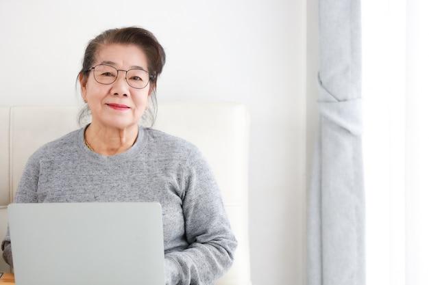 Aposentadoria asiática sênior da mulher usando o laptop na sala de estar Foto Premium