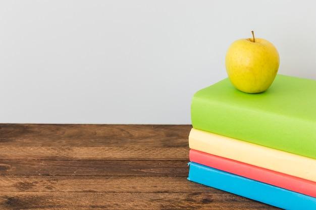Apple deitado em livros coloridos Foto gratuita