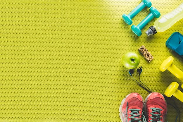 Apple e barra de energia perto de material esportivo Foto gratuita