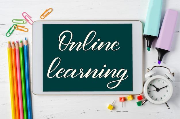 Aprendizagem online - inscrição manuscrita em um tablet. o conceito de treinamento à distância para crianças. tablet e material de escritório em um fundo branco de madeira. Foto Premium