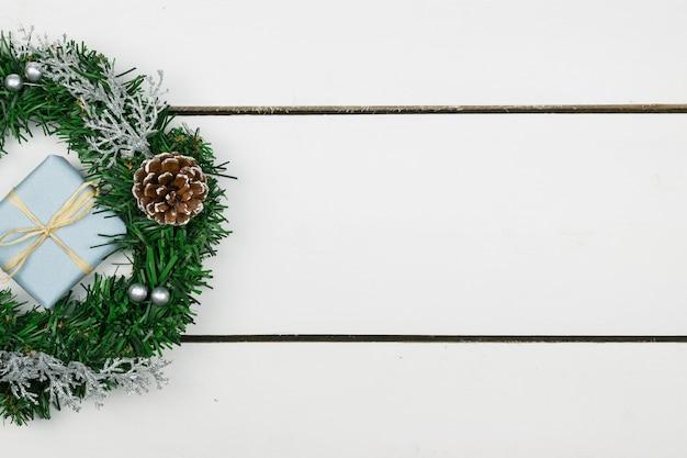 Apresenta com um ramo de pinheiro e decorações em um fundo de tábuas de madeira brancas Foto Premium