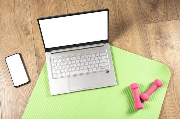 Aptidão de ioga online, maquete de laptop. halteres rosa, tapete de ginástica e laptop cinza no piso de madeira. conceito de treino online. Foto Premium