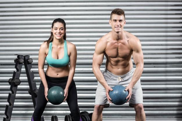 Apto casal fazendo exercício de bola no ginásio crossfit Foto Premium