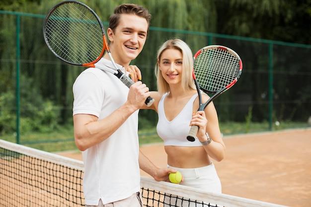 Apto casal jovem pronto para jogar tênis Foto gratuita